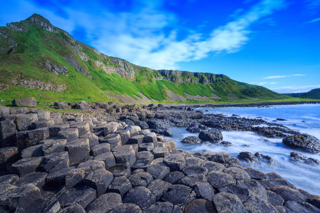 Giant's Causeway: geometric rock formations, green hills